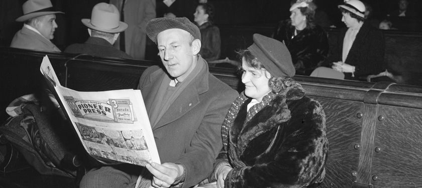 Historic photo of man and women reading newspaper in Waiting Room