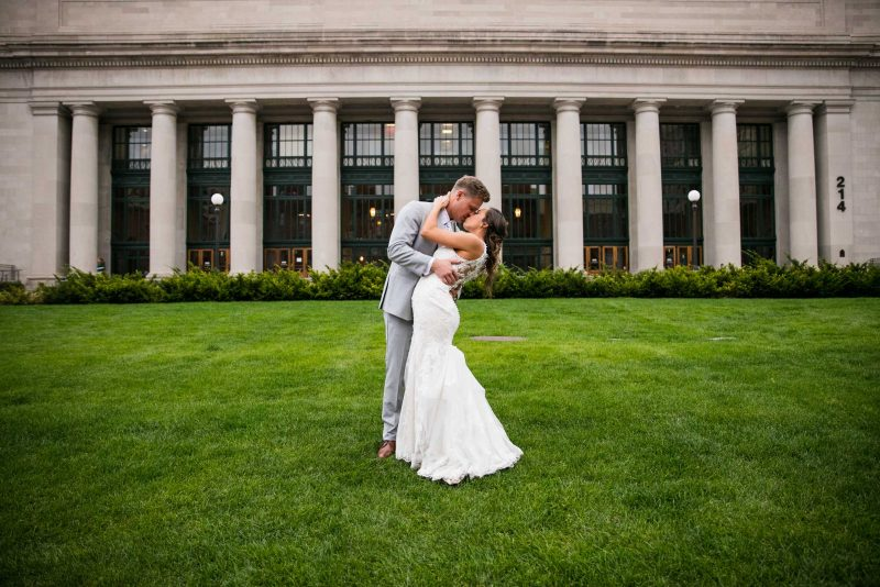 Bride and groom kissing on North Plaza lawn