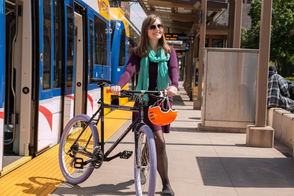 Woman walking bike off of transit